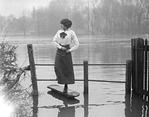 A woman crossing a stile after the flooding in the Thames Valley, December 1915